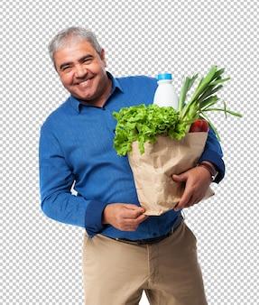 Mężczyzna trzyma torbę żywności