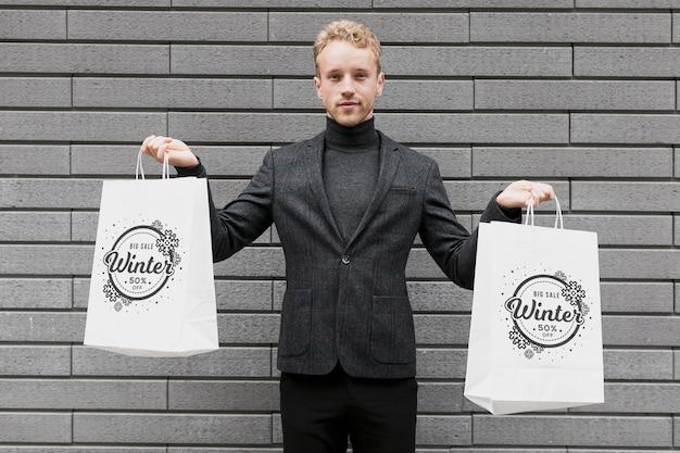 Mężczyzna trzyma w każdej ręce torby na zakupy
