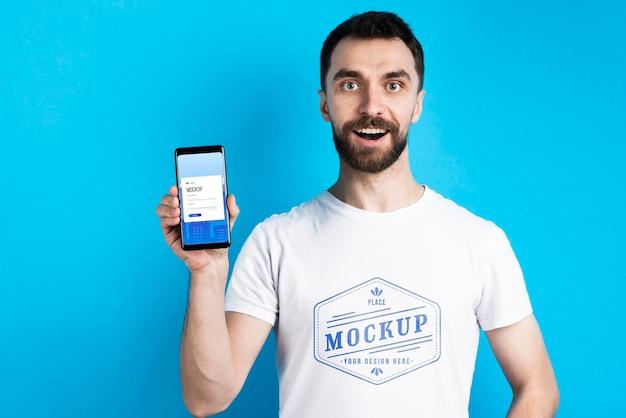 Mężczyzna w białej koszuli pokazuje telefon komórkowy średni strzał