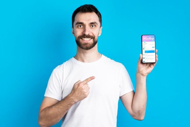 Mężczyzna w białej koszuli pokazuje widok z przodu telefonu komórkowego