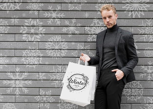 Mężczyzna w czarnym garniturze z torbami na zakupy