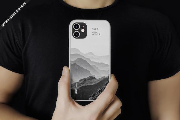 Mężczyzna w czerni pokazuje telefon w przypadku projektu makiety na białym tle