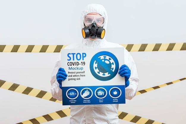 Mężczyzna w garniturze hazmat trzyma makietę koronawirusa stop