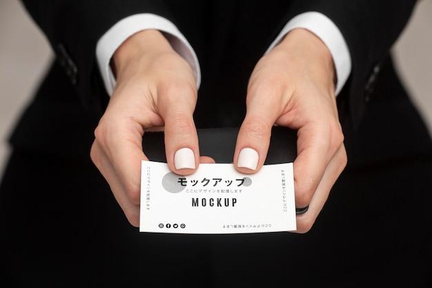 Mężczyzna w garniturze trzyma wizytówkę