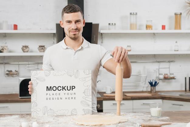 Mężczyzna w kuchni trzyma wałek do ciasta