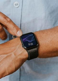 Mężczyzna w niebieskiej koszuli używający makiety smartwatcha