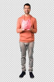 Mężczyzna w różowej bluzce biorąc skarbonkę i szczęśliwy, ponieważ jest pełna