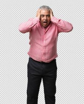 Mężczyzna w średnim wieku sfrustrowany i zdesperowany, zły i smutny z rękami na głowie