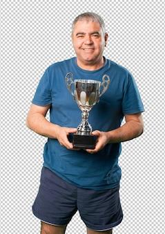 Mężczyzna w średnim wieku trzyma trofeum