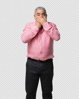 Mężczyzna w średnim wieku zakrywający usta, symbol ciszy i represji, starający się nic nie mówić