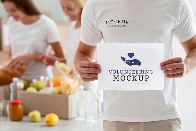 Mężczyzna wolontariusz trzymający czysty papier z kobietami przygotowującymi pudełka z darowiznami żywności