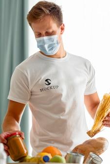 Mężczyzna-wolontariusz z maską medyczną przygotowuje pudełko na datki żywności