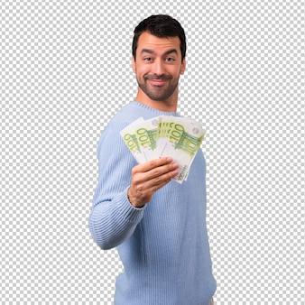 Mężczyzna z błękitnym pulowerem bierze mnóstwo pieniądze