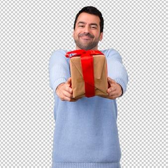 Mężczyzna z błękitnymi puloweru mienia prezenta pudełkami w rękach