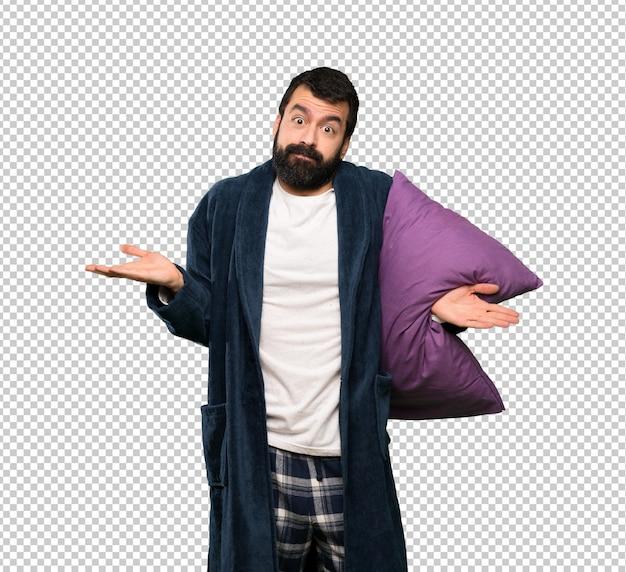 Mężczyzna z brodą w piżamach mający wątpliwości podczas podnoszenia rąk