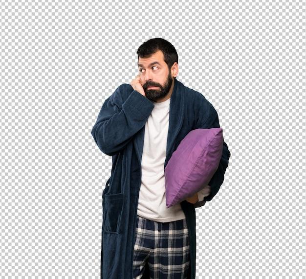 Mężczyzna z brodą w piżamie sfrustrowany i zakrywający uszy