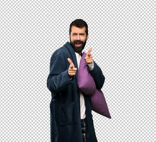 Mężczyzna z brodą w piżamie, wskazując na przód i uśmiechnięty