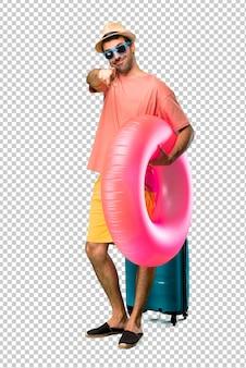 Mężczyzna z kapeluszem i okularami przeciwsłonecznymi na jego wakacje punktach dotyka przy tobą z ufnym wyrażeniem