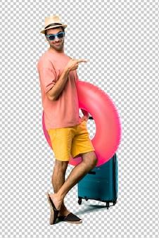 Mężczyzna z kapeluszem i okularami przeciwsłonecznymi na jego wakacje wskazuje strona z palcem przedstawiać produkt lub pomysł podczas gdy patrzejący do przodu ono uśmiecha się