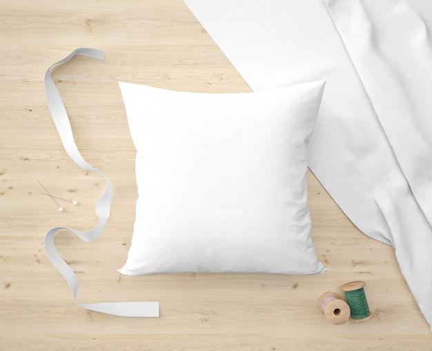 Miękka biała poduszka, wstążka i zielona nić