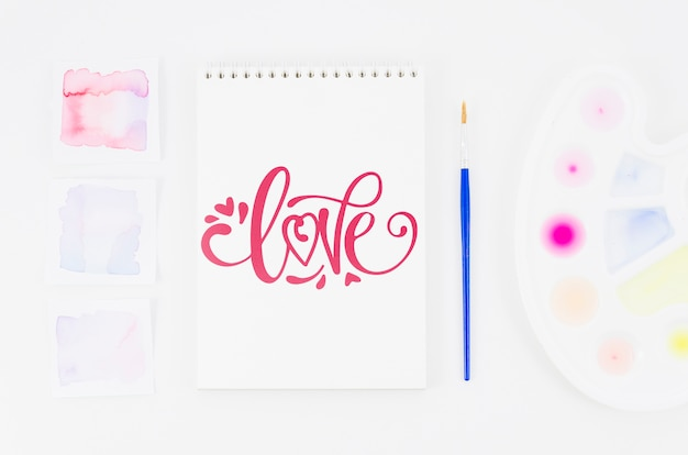 Miłość wiadomość na notebooku z pędzlem obok
