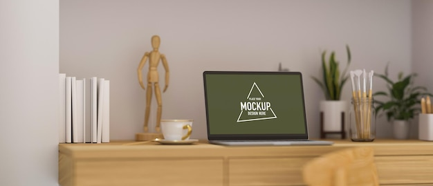 Minimalistyczny nowoczesny pusty ekran laptopa w przestrzeni roboczej na drewnianym wystroju stołu z drewnianą figurą