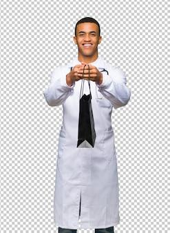 Młoda afro amerykańska mężczyzna lekarka trzyma mnóstwo torba na zakupy