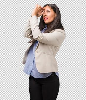 Młoda biznesowa indyjska kobieta patrzeje przez przerwy, chuje i mruży oczy