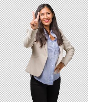 Młoda biznesowa indyjska kobieta pokazuje numer dwa, symbol liczenie, pojęcie matematyka, ufny i rozochocony