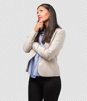 Młoda biznesowa kobieta indyjska wątpiąca i zdezorientowana, myśląca o pomyśle lub martwiona o coś