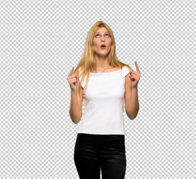 Młoda blondynki kobieta wskazuje w górę i zaskakujący