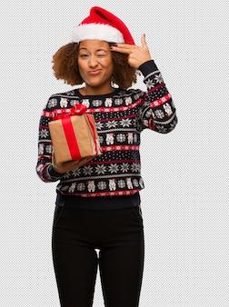 Młoda czarna kobieta trzyma prezent w święta bożego narodzenia robi samobójstwo gestowi