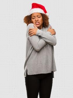 Młoda czarna kobieta w kapeluszu santa będzie zimno ze względu na niską temperaturę