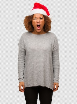 Młoda czarna kobieta w kapeluszu santa krzyczy bardzo zły i agresywny