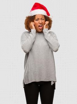 Młoda czarna kobieta w kapeluszu santa obejmujące uszy rękami