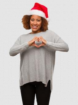 Młoda czarna kobieta w kapeluszu santa robi kształt serca z rękami