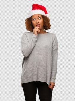 Młoda czarna kobieta w kapeluszu santa wątpiąc i zdezorientowany