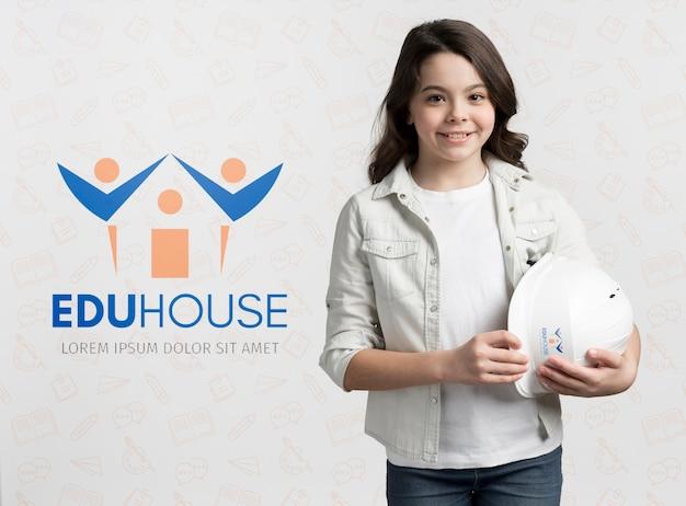 Młoda dziewczyna trzyma hełm budowy