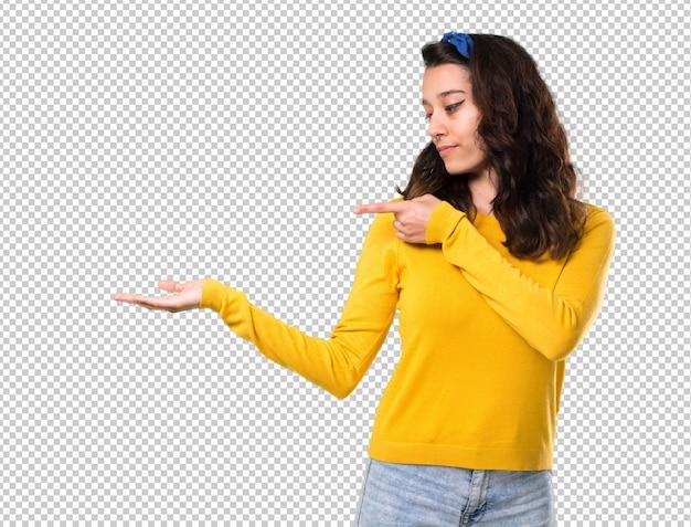 Młoda dziewczyna z żółtym swetrem i niebieską chustka na głowie gospodarstwa copyspace