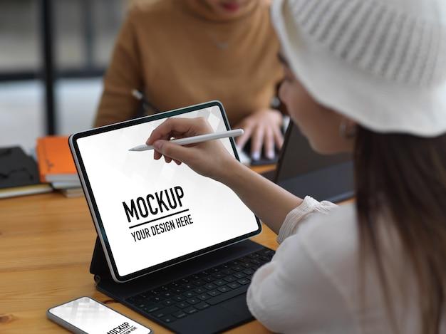 Młoda kobieta pracuje na makieta tablet z ekranem w wygodnym obszarze roboczym