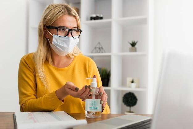Młoda kobieta przy biurku z makietą maski i środka dezynfekującego