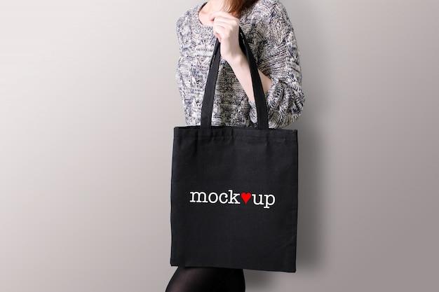 Młoda kobieta trzyma czarną torbę, makieta.