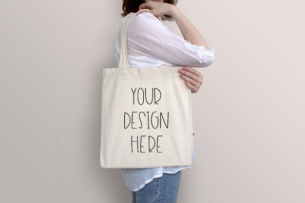 Młoda kobieta trzyma dużą torbę, makieta
