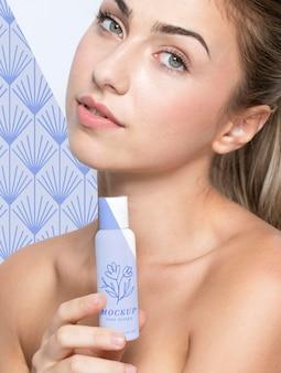 Młoda kobieta trzyma makietę produktu do pielęgnacji skóry