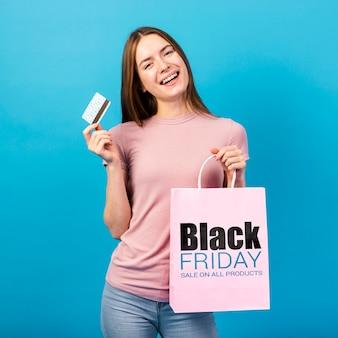 Młoda kobieta trzyma papierową torbę i kartę kredytową