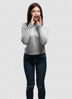 Młoda ładna kobieta krzyczy szczęśliwa, zaskoczona ofertą lub promocją, rozdziawiona, skacząca i dumna