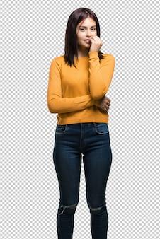 Młoda ładna kobieta obgryzająca paznokcie, nerwowa i bardzo niespokojna, bojąca się o przyszłość, odczuwa panikę i stres