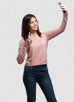 Młoda ładna kobieta pewna siebie i wesoła, robi selfie, patrzy na telefon z zabawnym i beztroskim gestem, surfuje po sieciach społecznościowych i internecie