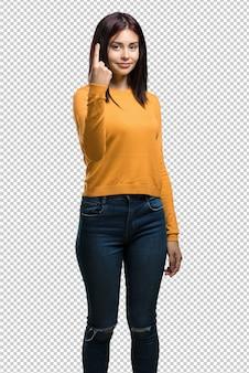 Młoda ładna kobieta pokazuje liczbę jeden, symbol liczenie, pojęcie matematyka, ufny i rozochocony