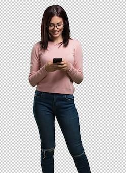 Młoda ładna kobieta szczęśliwa i zrelaksowana, za pomocą telefonu komórkowego
